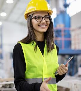 Bella ragazza in fabbrica in gilet e casco sorridente che va a farsi una stretta di mano