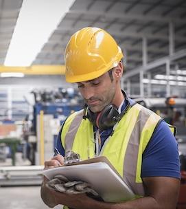 Male worker writing on clipboard in factory